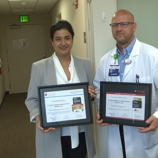 Pawani Sachar, M.D., neurologist at Providence Medical Group-South, and Bryan Jensen, heart and vascular manager at Providence Medford Medical Center, display the award from the American Heart Association.
